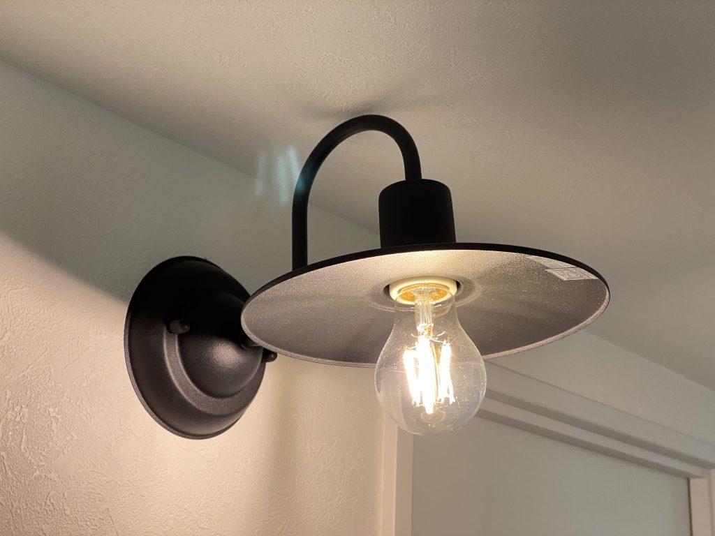 建具のアイアン部分と呼応するように取り付けられたブラケットライト。広範囲を温かな光で照らします。黒いアイアンが空間を引き締める効果も。
