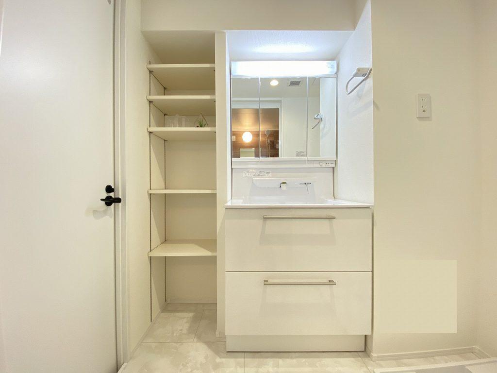 洗面化粧室の様子です。天井まであるオープン棚の収納完備。可動棚なので、リネンをはじめ洗剤等を収めていただけます。