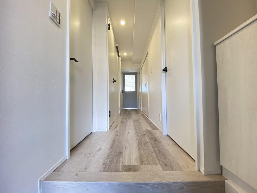 玄関からリビングにつながる玄関ホールの様子です。床材と建具が温かな雰囲気を感じさせる印象。