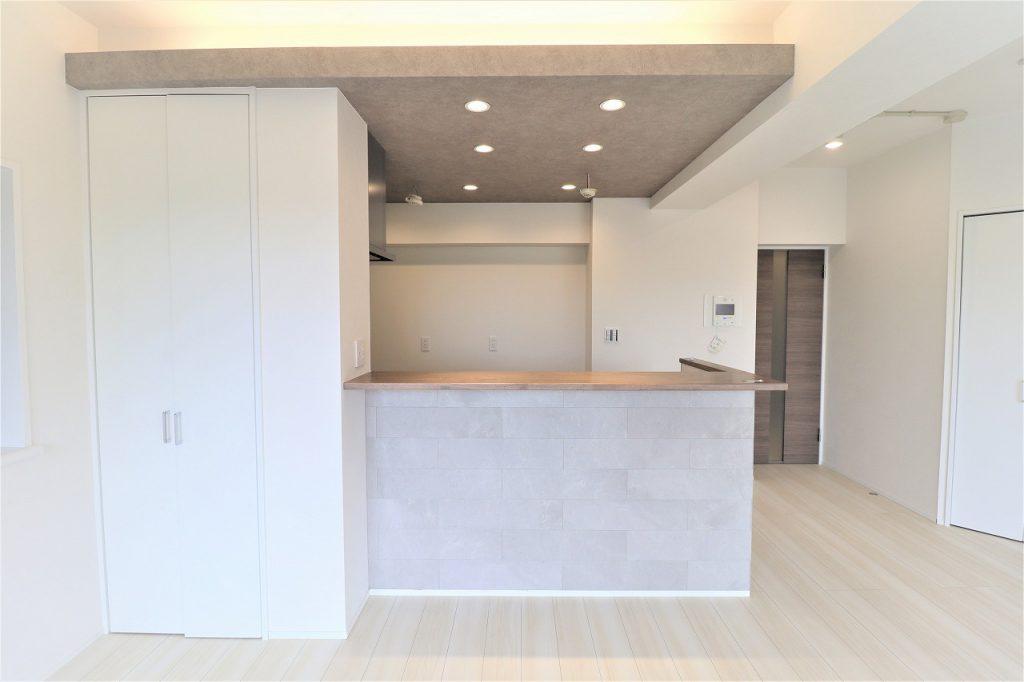 ダイニングから見たキッチンの様子です。ストーン柄のエコカラットをパネリングしていますので、調湿・消臭効果も加味した意匠性。収納もありますので、お部屋に物が散らかることも防げます。