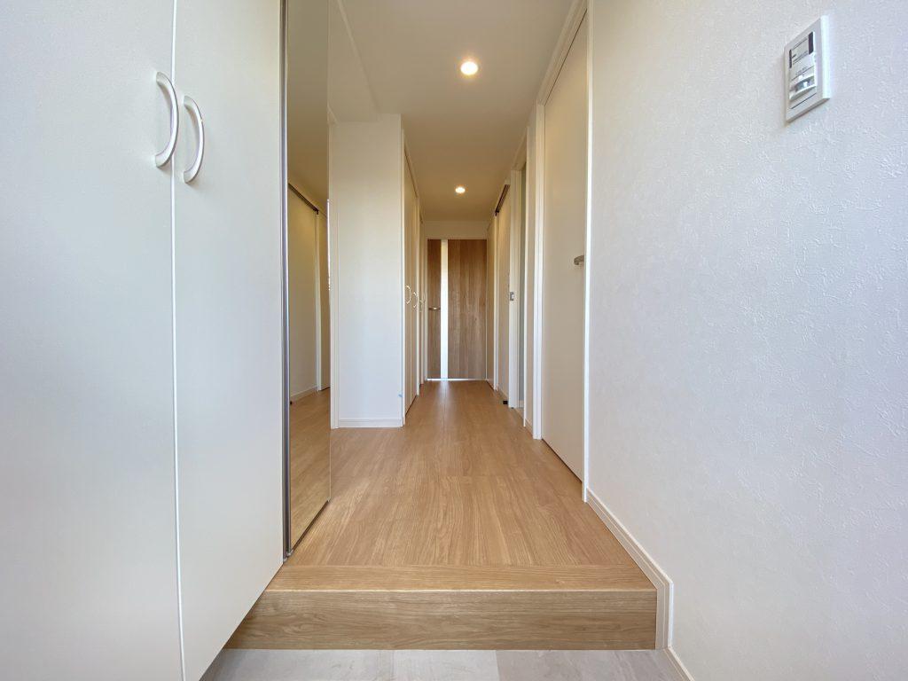 玄関からリビングに向かう室内廊下部分の様子です。床材とクロスのコーディネイトが明るい雰囲気を演出しています。
